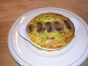 Eggplant Frittata: a baked omelet with sauted eggplant, mushrooms and scallion, the egg is infused with cheddar and parmesan cheeses, topped with a spoon full of basil pesto.
